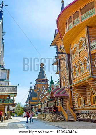 MOSCOW RUSSIA - MAY 10 2015: The timbered wall of Tsar's Palace in Izmailovsky Kremlin with the St Nicholas Church on the background on May 10 in Moscow.