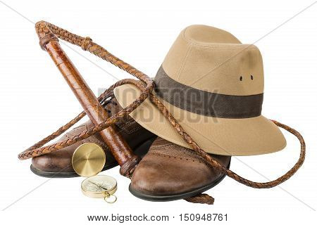 Travel and adventure concept. Vintage brown shoes with fedora hat bullwhip and compass isolated on white background
