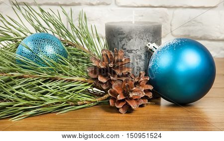 New Year and Christmas composition with fir cones and candle on wooden and brick background