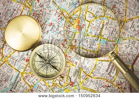 Tourism concept. Magnifying glass with compass on city map.