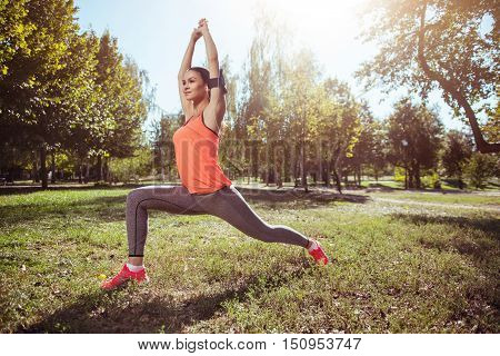 Harmony and balance. Young beautiful athletic girl making lunge while having yoga as her morning training and using headphones.