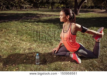 Harmony of nature. Pretty young active girl doing stretching while training in the park wearing headphones and sportswear.