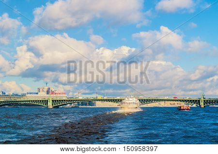 ST PETERSBURG RUSSIA-OCTOBER 3 2016. Trinity Bridge and touristic pleasure boat floating under the bridge span at Neva River in St Petersburg. St Petersburg city landscape in sunny day
