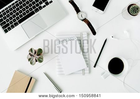Flat lay top view office table desk. Workspace with laptop diary phone coffee succulent and watch on white background.