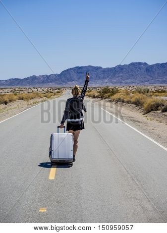 young woman walking with her suitcase on a desert road rising her arm for victory
