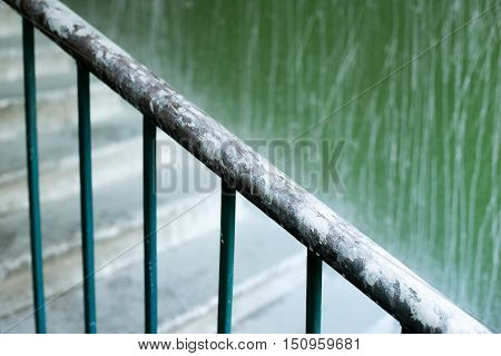 Close up of a railing on the stairs. The steps covered in whitewash, dirt. Renovation of the house.