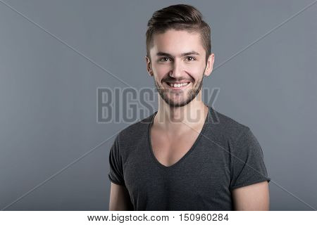 Happiness in mind. Amused young bearded man smiling while standing against grey background