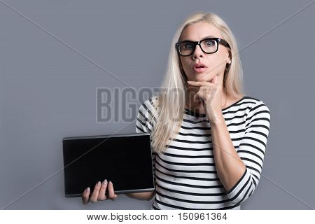 Impressive qualities of modern devices. Puzzled young woman holding the tablet and raising one hand to her opening mouth while standing against grey background