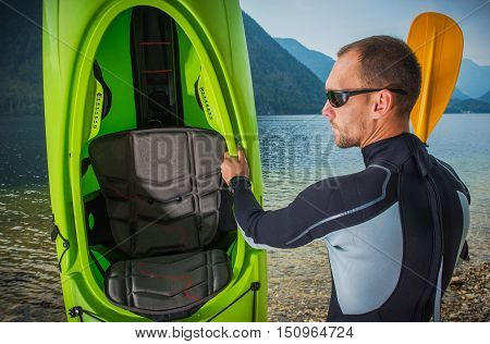 Sportsman in Wetsuit with His Kayak Closeup Photo. Kayaking and Water Sports Theme.