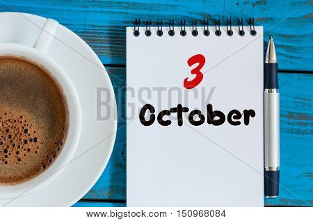 October 3rd. Day 3 of month, calendar on notepad with morning cup coffee or tea at student workplace background. Autumn time.