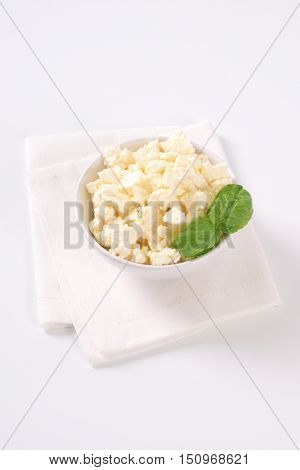bowl of crumbled feta cheese on white place mat