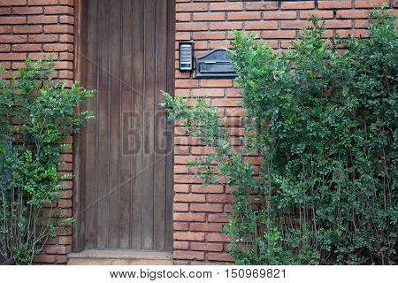 Wooden door entry with mailbox and intercom on a brick wall