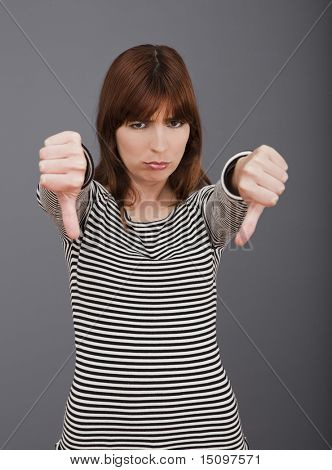 Young woman expressing negativity with thumb down over a grey background