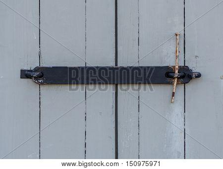 Wrought Iron Door Latch on gray wooden building
