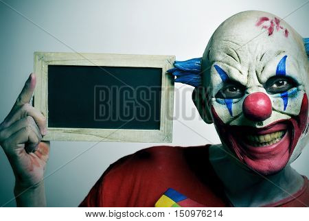 portrait of a scary evil clown with a blank wooden-framed chalkboard
