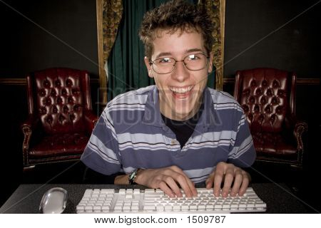 Happy Teenage Boy On Computer