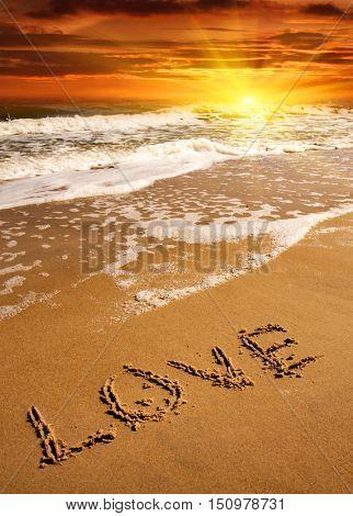 love word on sea beach on sunset background