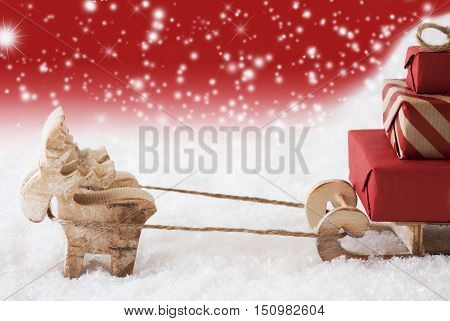 Moose Is Drawing A Sled With Red Gifts Or Presents In Snow. Christmas Card For Seasons Greetings. Red Christmassy Background With Snowflakes. Copy Space For Advertisement