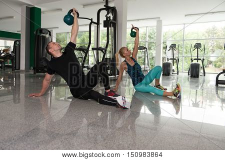 Healthy Young Couple Doing Exercise With Kettle Bell