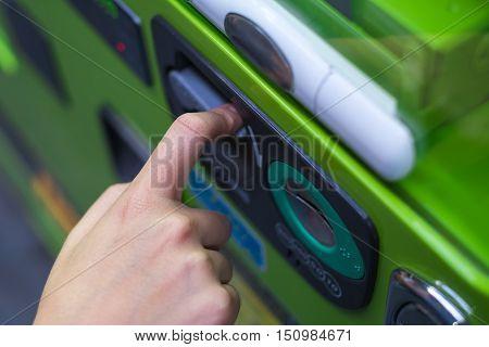 Hand pushing refund bar on vending machine.