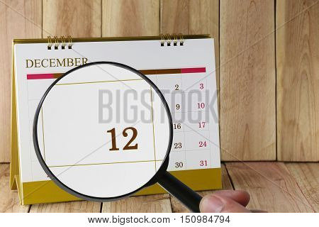 Magnifying glass in hand on calendar you can look Twelfth date of monthFocus number twelve in DecemberConcept in business and meetings.