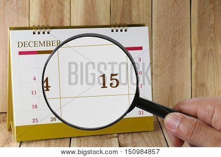 Magnifying glass in hand on calendar you can look Fifteenth date of monthFocus number fifteen in DecemberConcept in business and meetings.