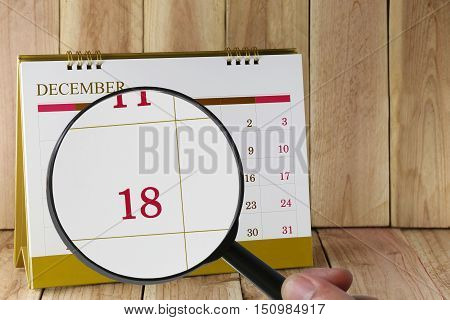Magnifying glass in hand on calendar you can look Eighteenth date of monthFocus number Eighteen in DecemberConcept in business and meetings.