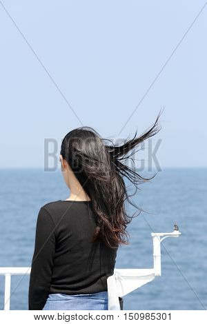 Back view of young asian woman with waving long hair from the deck