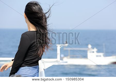 Back view of young asian woman with waving long hair from the deck of cruise ship