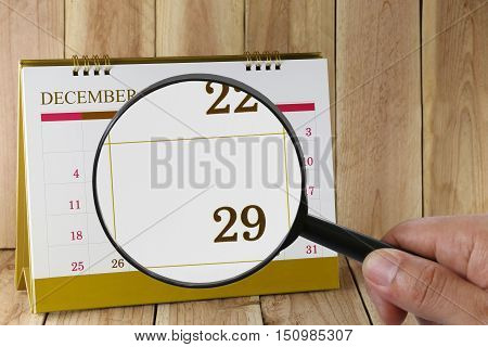 Magnifying glass in hand on calendar you can look Twenty-nine date of monthFocus number Twenty-nine in DecemberConcept in business and meetings.