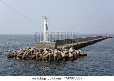 white lighthouse with jetty in the sea