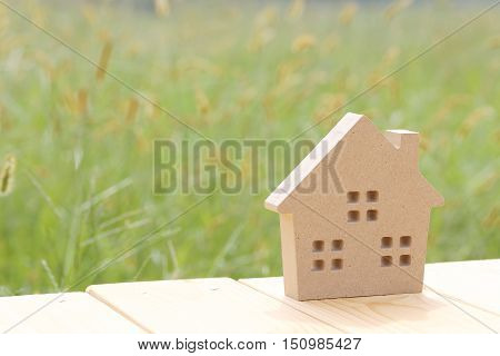 toy wooden house in green grass on sunshine