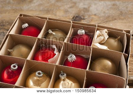 Open cardboard carton of rustic golden and red colored christmas tree ornaments balls on table