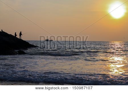 a silhouette of a fisher at sunset on a seashore. Sunset landscape of sea with fisherman standing on rock southern Thailand Phuket Island