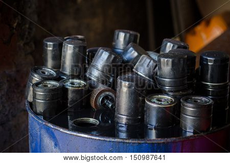 Closeup picture of old and dirty car oil filter. Automotive maintenance service concept.
