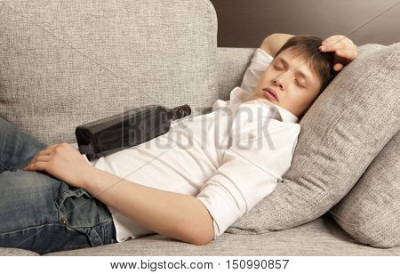 Drunkard. A young man with a drinking problem is relaxing on a sofa