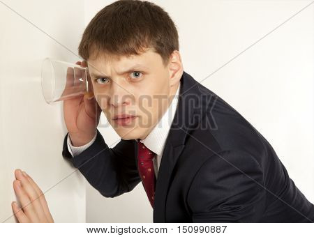Business spy concept - businessman spying by listening through wall with glass