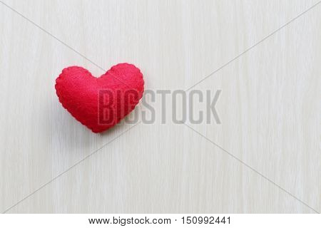 Red heart is placed on a wooden floor concept of love in Valentine's Day.