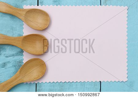 Wooden spoon on pink note paper and blue wood tableconcept of utensils and cooking.