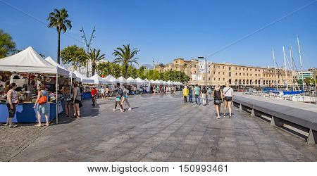 BARCELONA SPAIN - JULY 4 2016: Promenade along Port Vell near the Museum of History (Palau de Mar 1880-1890) in front of the harbor.