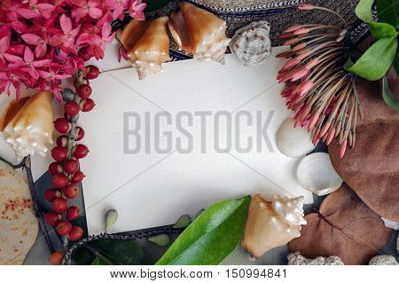 Mock-up - empty paper note, view from above, framed sea shells, tropical flowers, leaves, berries. Caribbean vacation theme. Toned.