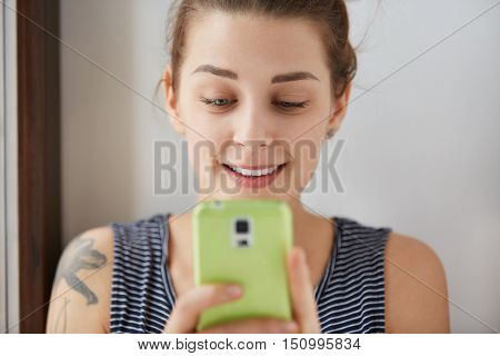 Close-up Portrait Of European Girl Playing Games At Her Green Smartphone. Young And Charming Woman H