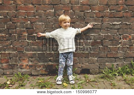 Portrait Of Happy Careless Little Boy. Tiny Kid Standing Near Brick Wall, Stretching Arms Outside. H