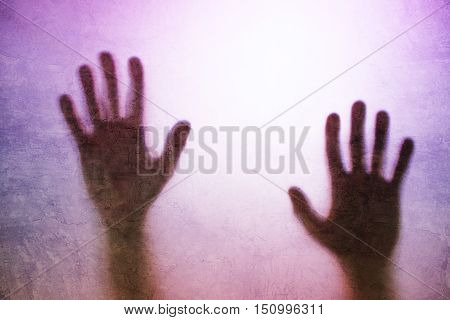 Trapped person concept with back lit silhouette of hands behind matte glass useful as illustrative image for human trafficking prostitution imprisonment mental illness captivity depression.