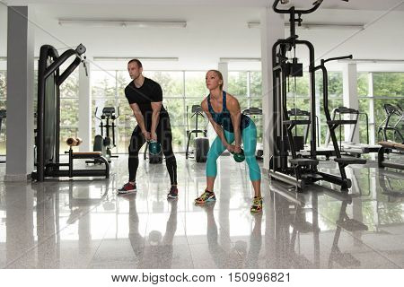 Couple Doing Heavy Weight Exercise With Kettle-bell