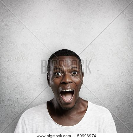 Human Face Expressions And Emotions. African Customer Or Employee Dressed Casually Looking In Surpri