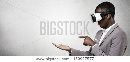 African-american Man In Formal Wear Using 3D Virtual Reality Headset For Smart Phone. Black Gamer We