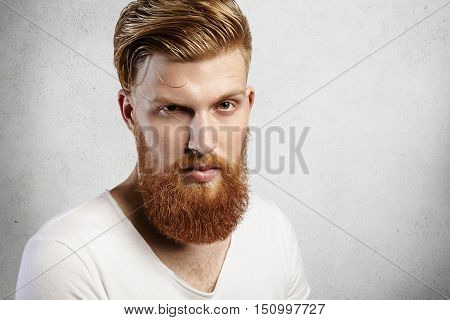 Close-up Portrait Of Young Caucasian Man With Long Ginger Beard And Trendy Hairstyle. Young Hipster