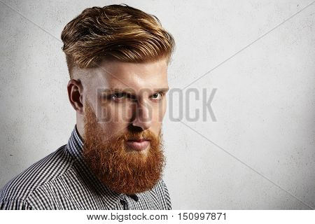 Manful European Hipster In Checked Shirt Looking Seriously At The Camera. His Stylish Haircut And We