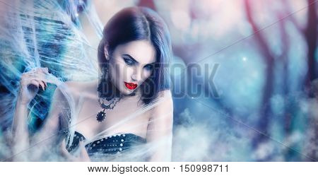 Fantasy Halloween Vampire woman portrait. Beauty Sexy Vampire Witch lady posing in deep forest, wearing spider web. Fashion Art design. Beautiful Gothic model girl with Halloween make up and costume